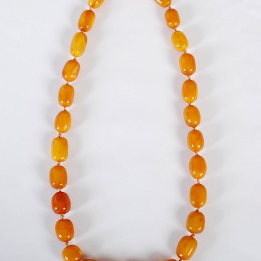A graduated amber necklace, 114 grams, sold for £2,400