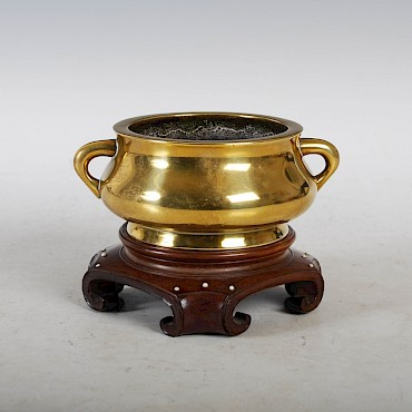 A Chinese bronze censer and dark wood stand, bearing six character Xuande mark, sold for £2,550