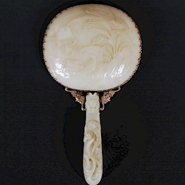 A Chinese pale celadon jade and silver mounted hand mirror, Qing Dynasty, sold for £5,300
