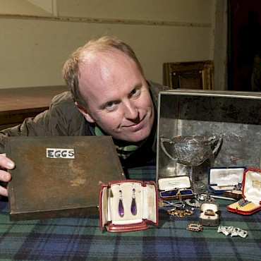 Auctioneer Nick Burns with the metal box and the Jewellery which was fouind inside.