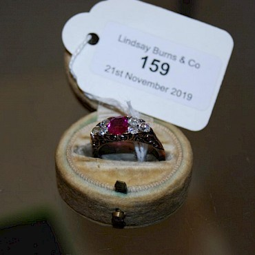 Lot 159. A ruby and diamond cluster ring, sold for £440